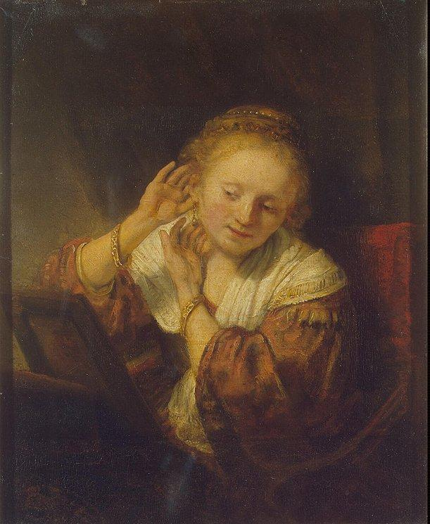 Young Woman Trying Earrings - Rembrandt