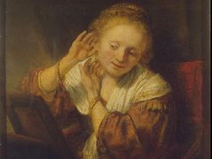 Young Woman Trying Earrings – Rembrandt