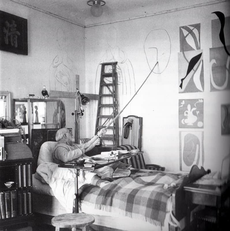 Matisse working on his artwork in bed